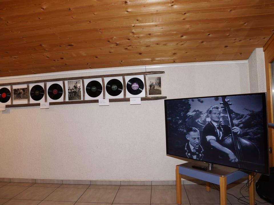 Man sieht eine Menge Schallplatten an der Wand aufgehängt und ein grosses Bild von Giovanelli