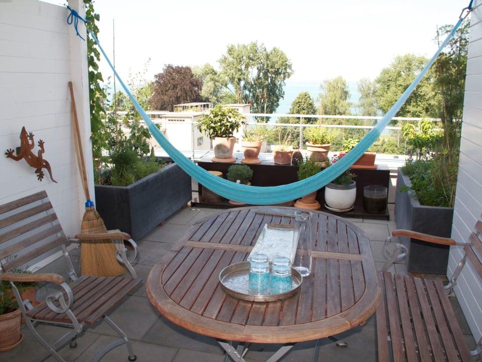 Balkon mit Tisch und Hängematte, im Hintergrund der See.