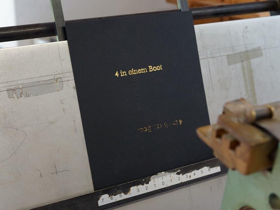 Auf einem schwarzen Buchdeckel steht in goldener Schrift «4 in einem Boot».