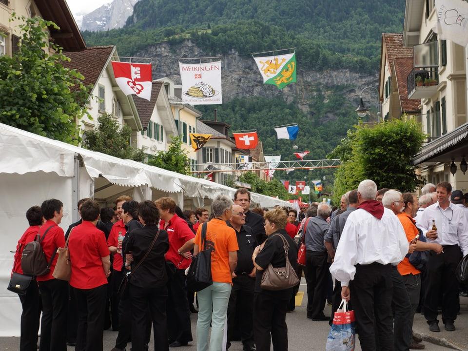 Viele Menschen auf einer mit Fahnen geschmückten Strasse.