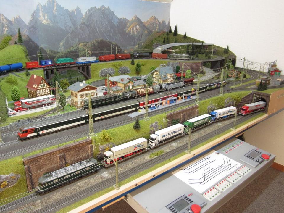 MIt Blick auf unzählige Knöpfe und Schalter am Rand der MOdelleisenbahn.