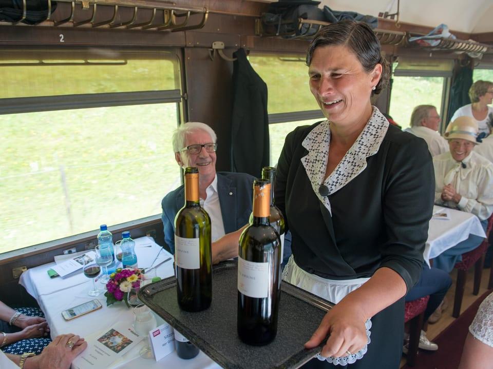 Eine Frau als Serviertochter balanciert ein Tablett mit zwei Flaschen Wein in einem Zug-Speisewagen