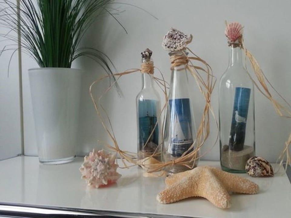 Drei Glasflaschen mit Gutschein darin.