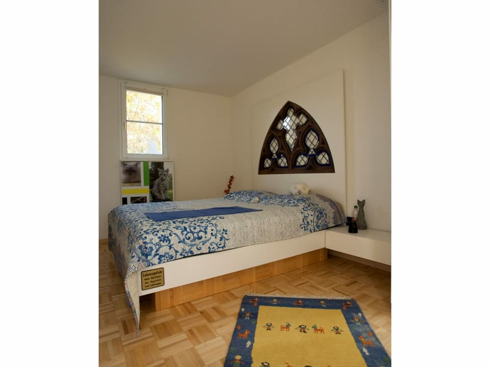 Doppebett mit Bettvorleger auf sehr engem Raum.