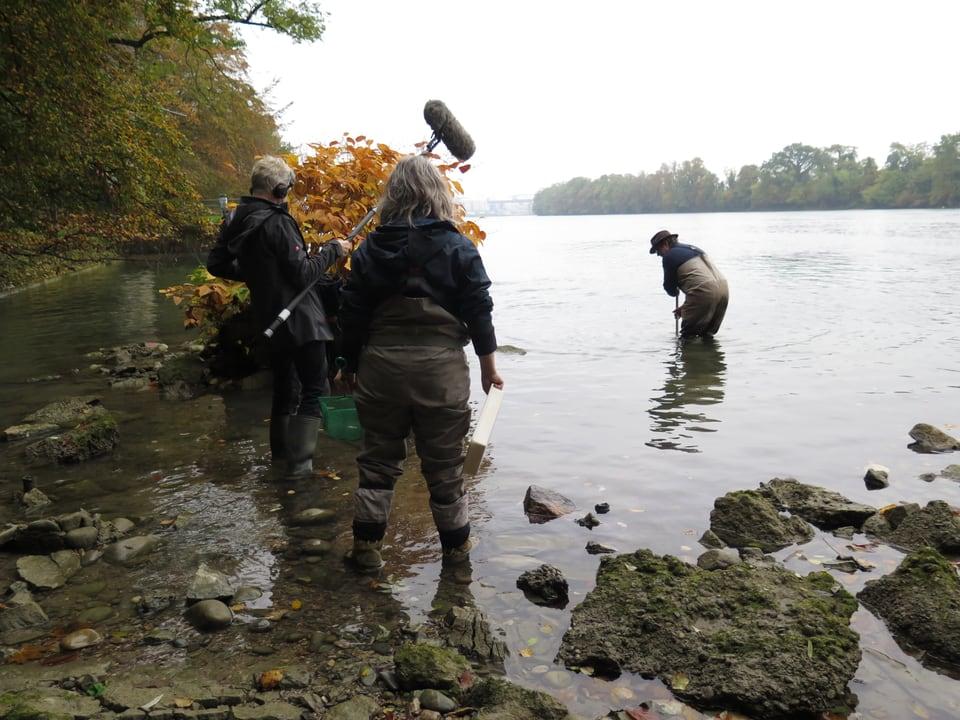 Ein Mann mit Mikrofon, eine Frau un ein Mann mit Fischernetz stehen in Wasser.