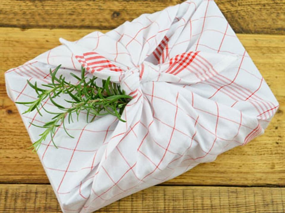 Küchentuch um ein Geschenk gewickelt, verziert mit Rosmarinzweig.