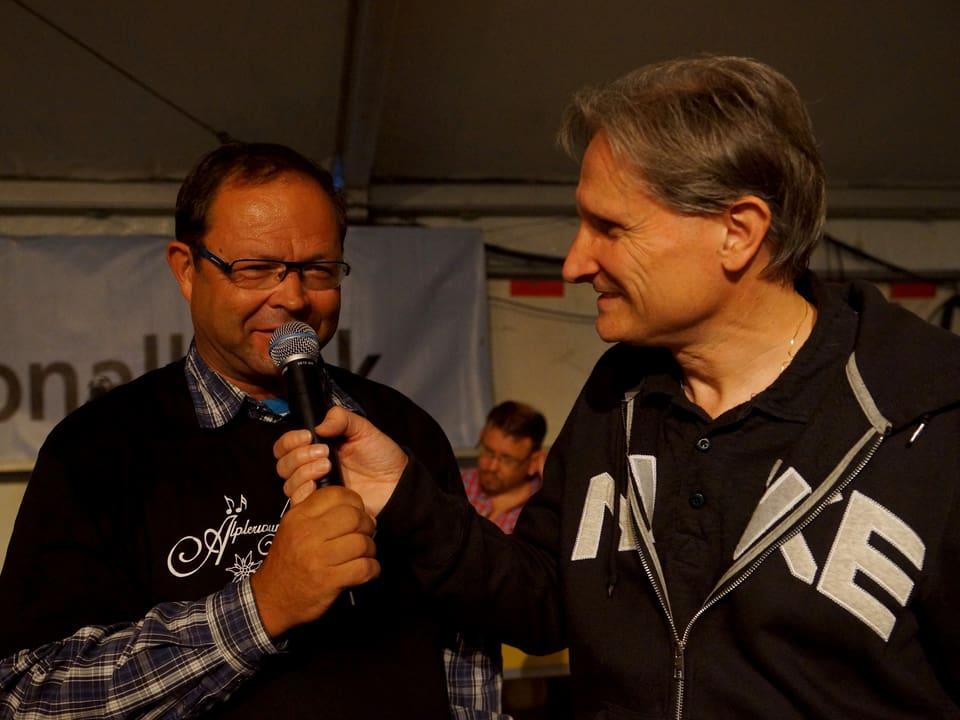 Moderator Beat Tschümperlin hält Sepp Hess das Mikrofon hin.