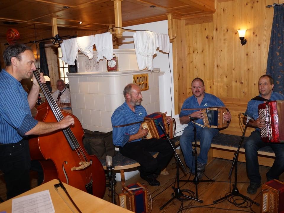 Ein Bassgeiger, zwei Schwyzerörgeler und ein Akkordeonist beim Musizieren in einer Gaststube.