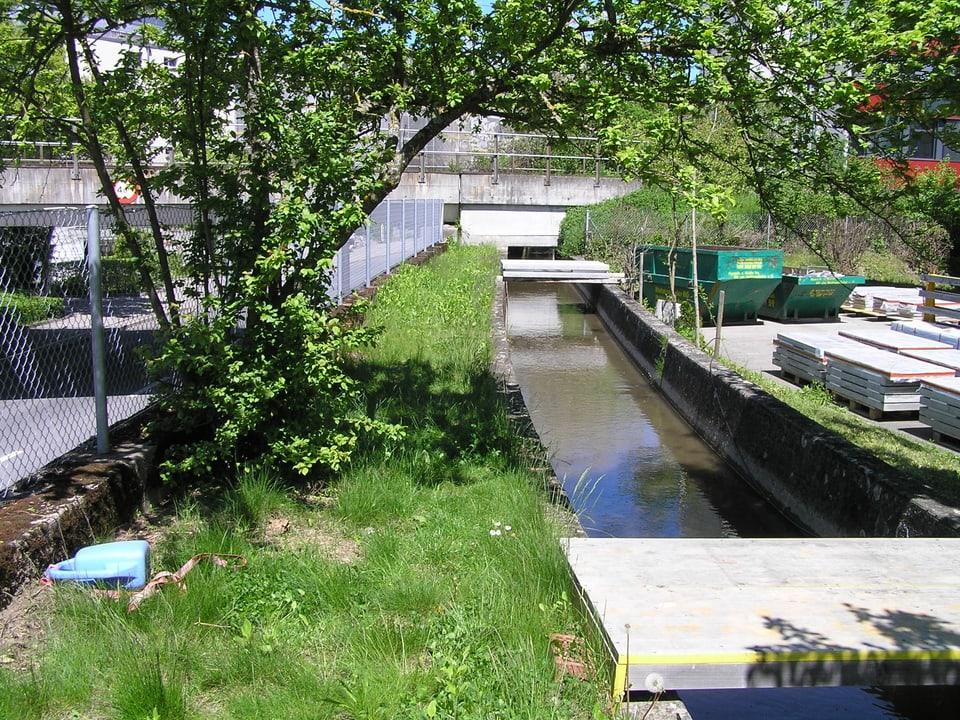 Der kanalisierte Stadtbach von Bümpliz mit einem schmalen Grasstreifen links und eine kleinen flachen Brücke.