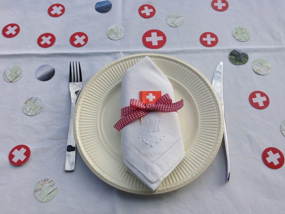 Teller mit Besteck und Deko auf einem Tisch.