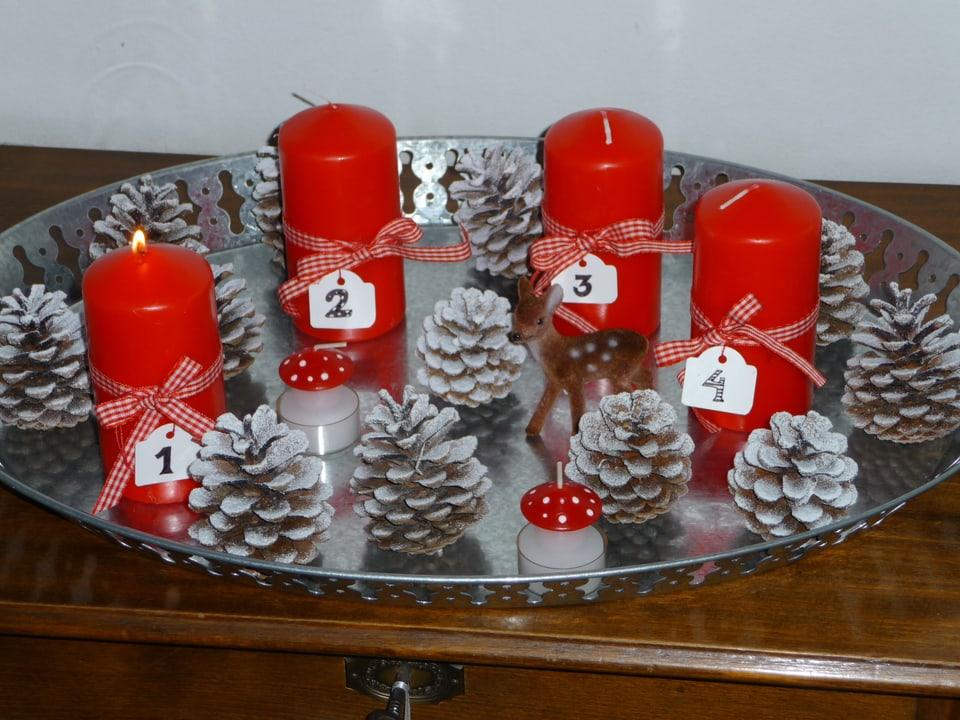 Föhrenzapfen mit vier roten Kerzen auf einem Tablett.