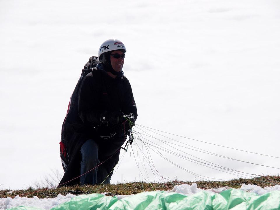 Stefan Keller hält die Seile seines Gleitschirmes in der Hand.