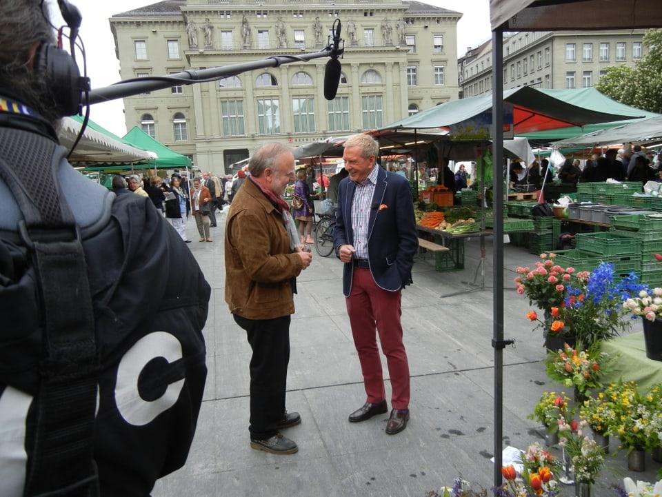 Peter Reber und Kurt Aeschbacher im Gespräch auf dem Bundesplatz. Im Vordergrund ist die Perche (Mikrofonstange) des Tonoperateurs zu sehen. Verschieden farbige Blumensträusse stehen auf dem Boden.