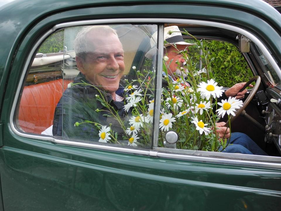 Kurt Aeschbacher lächelt verschmitzt vom Beifahrersitz des grünen Fiat Topolinos. Er hält einen Margeritenbusch auf dem Schoss. Francesco Di Cesare steuert den Oltimer mit Jahrgang 1952.