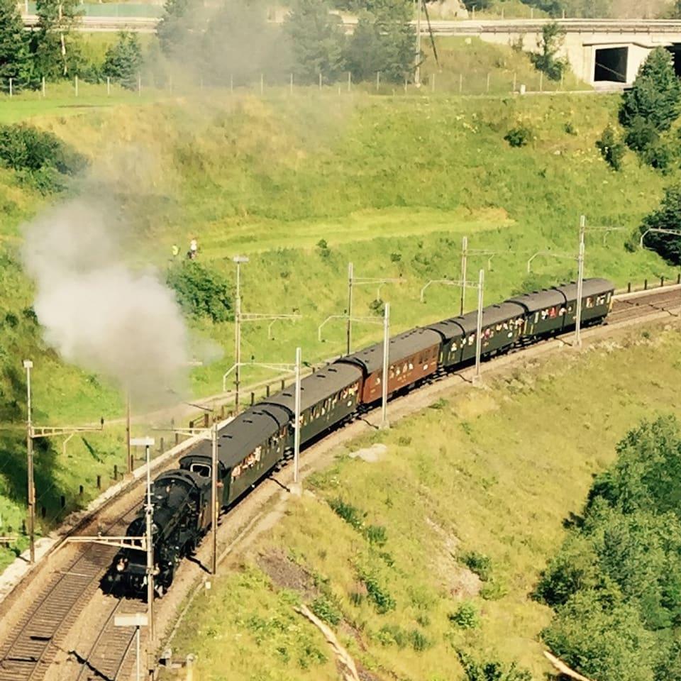 Dampflok zieht historische Zugswagen durch eine grüne Landschaft