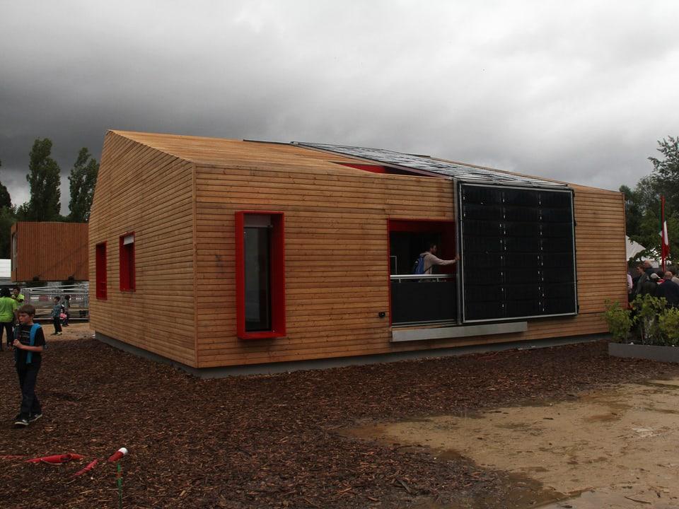 Modell-Haus mit Solarzellen und viel Holz.