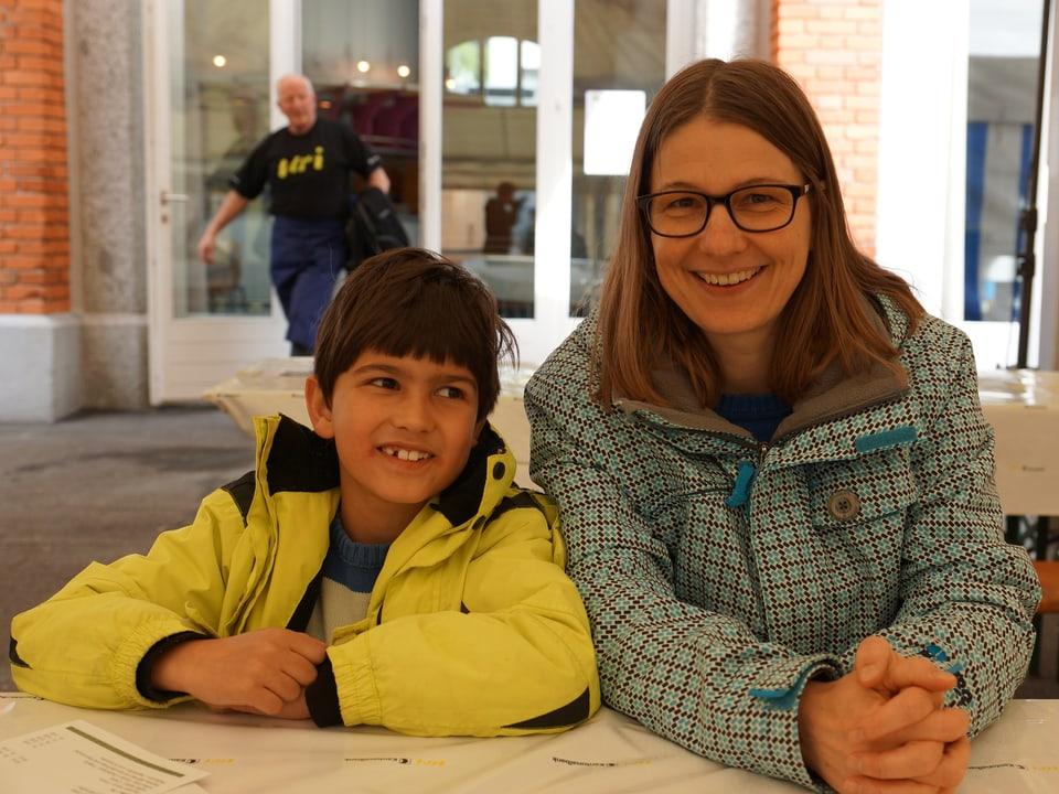 Sohn und Mutter sitzen in warmen Jacken am Tisch im Festzelt.
