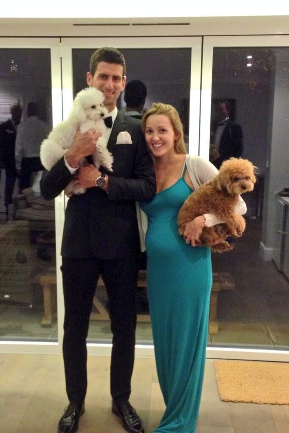 Novak Djokovic und Jelena Ristic lächelnd und Pudeln auf dem Arm.