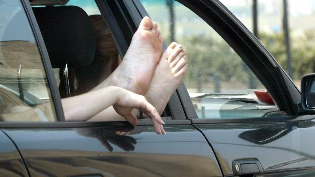 Eine Frau hält die Füsse aus einem Autofenster.