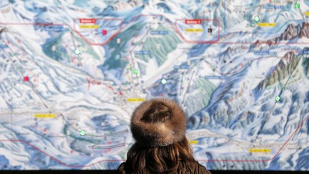 Eine Frau in Pelz von hinten: Sie betrachtet die Karte eines Skigebiets..