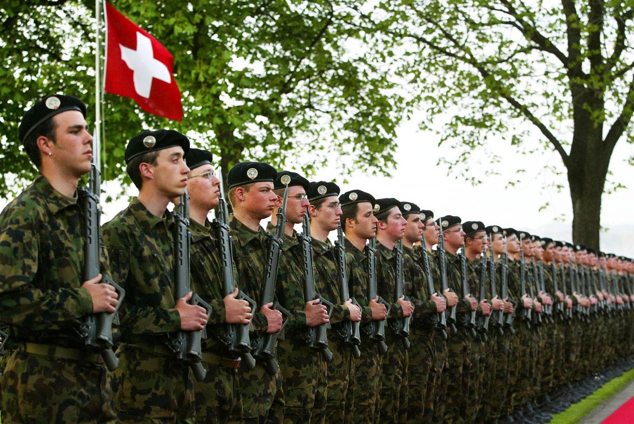 Rekruten stehen in einer Reihe im Hintergrund eine Schweizer Fahne