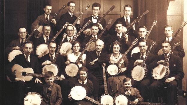 Gruppenbild: Frauen und Männer sitzen und stehen mit ihren Banjos.