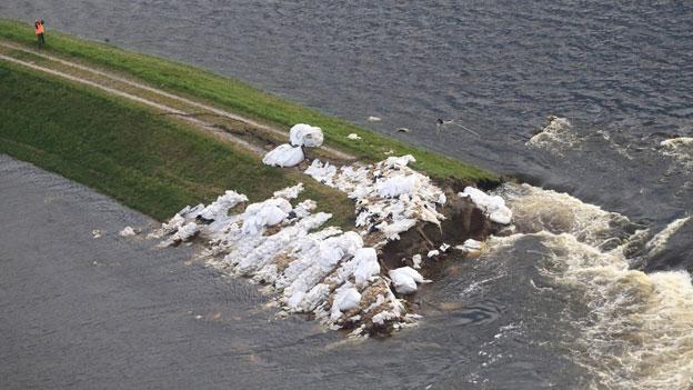 Das Wasser kam so schnell, die Leute konnten kaum etwas mitnehmen. Bild:  Flusswasser strömt über einen gebrochenen Deich in der Elbe in der Nähe von Fischbeck, Deutschland, am 15. Juni 2013.