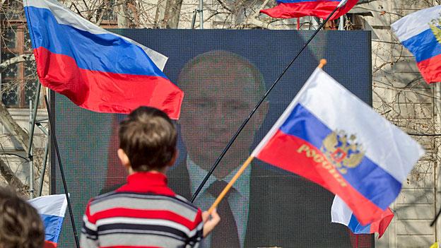 Russinnen und Russen hören der Rede ihres Präsidenten zu.