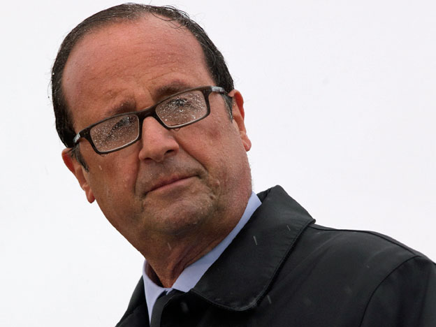 Frankreichs Präsident François Hollande steht im Regen.