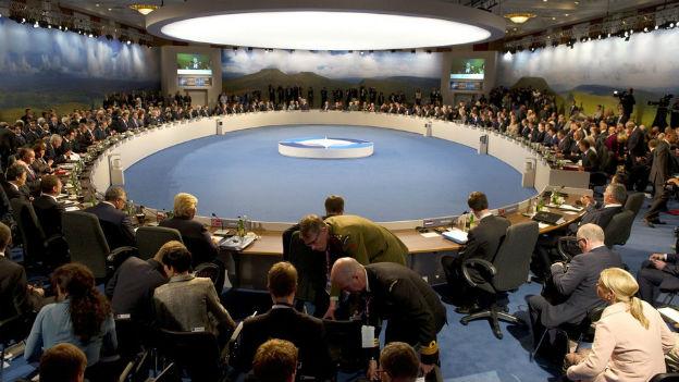 Vertreter von Nato-Mitgliedsländern sitzen an einem grossen runden Tisch in einem grossen Sitzungszimmer.