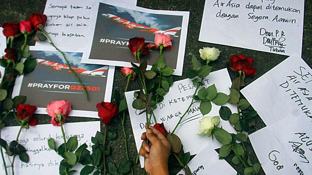 Blumen und Kondolenzbekundungen für die Passagiere der abgestürzten Air-Asia-Maschine; es scheint keine Überlebenden zu geben.