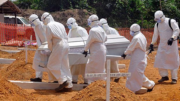 Gesundheitsarbeiter in weissen Schutzanzügen tragen den Sarg eines Ebola-Opfers auf einen Friedhof. Im März 2015 in der liberianischen Hauptstadt Monrovia.