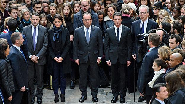François Hollande und weitere Mitglieder der französischen Regierung haben sich zu einer Schweigeminute versammelt,