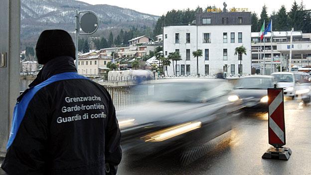 Ein Mitglied der Grenzwache beobachtet den Strassenverkehr an der Grenze in Ponte Tresa.