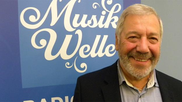 Alex Eugster mit Bart vor dem blau-weissen Logo der SRF Musikwelle.
