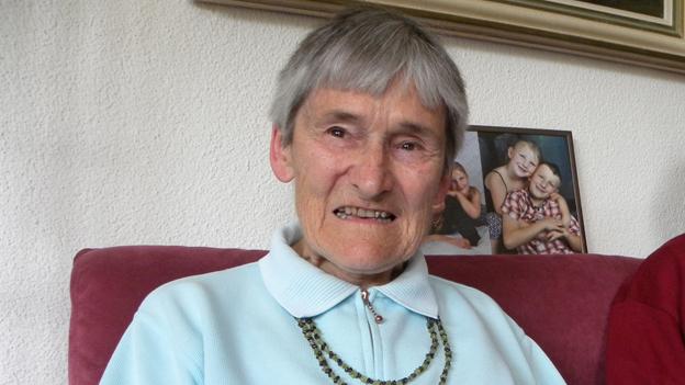 Die Seniorin trägt einen hellblauen Pullover und sitzt auf einem altrosa-farbenen Sofa.