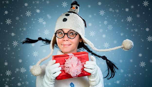 Ein Mädchen mit einer lustigen Zottelmütze hält ein rot eingepacktes Geschenk in der Hand.