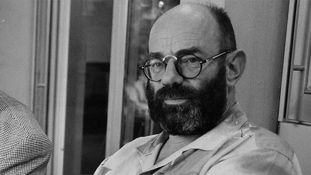 Schwarz-Weiss-Fotografie von einem bärtigen Mann mit Brille.