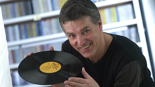 Der Redaktor hält eine Schallplatte in der Hand.