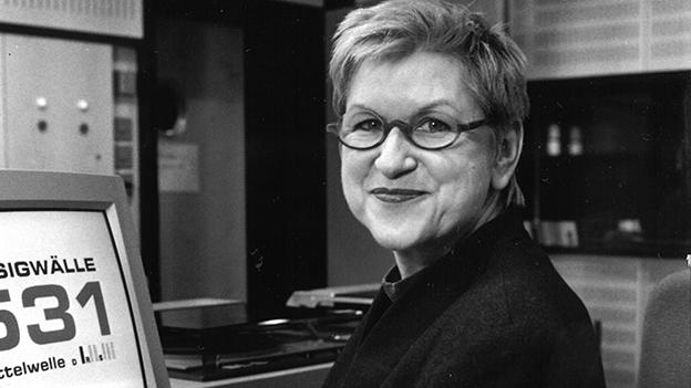 Schwarz-Weiss-Fotografie von der Moderatorin, die im Radiostudio vor dem Mikrofon sitzt.