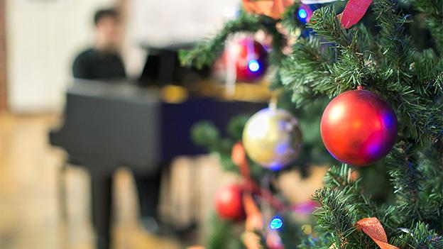 Ein Weihnachtsbaum, im Hintergrund ein Klavier.
