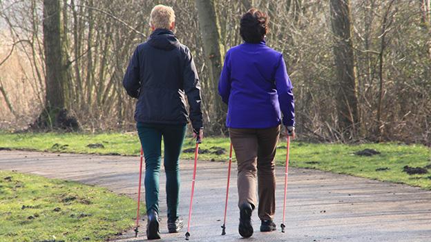 Zwei Frauen unterwegs mit Nordic Walking Stöcken.