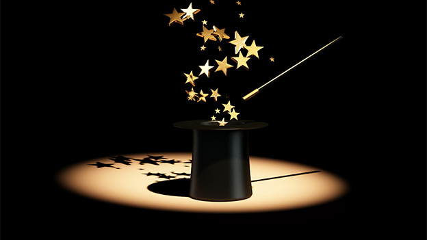 Aus einem Zylinder fliegen goldene Sterne.