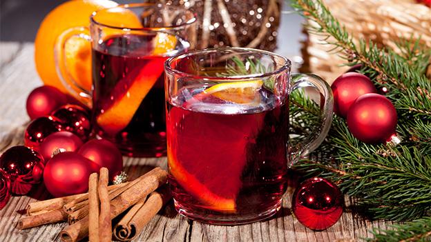 Zwei Gläser mit Punsch inmitten einer Weihnachts-Dekoration.