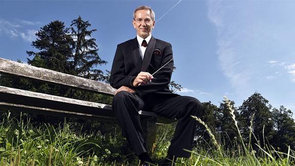 Ein Mann im Anzug und mit Dirigentenstab sitzt auf einer Holzbank.