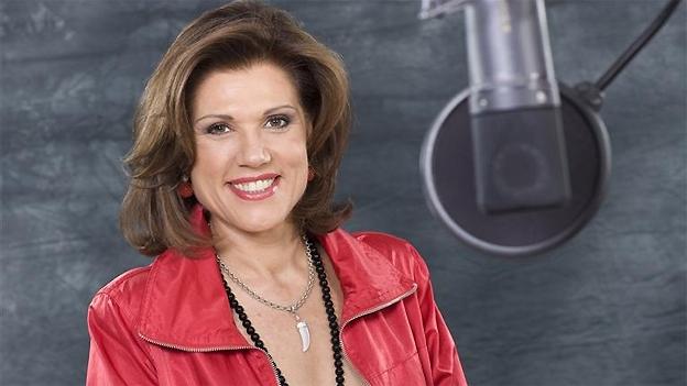 Eine Frau mit schulterlangen Haaren und einer roten Jacke.