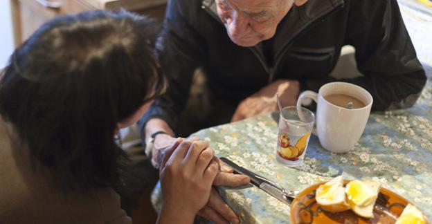 Eine Frau betreut einen älteren Mann beim Nachtessen.