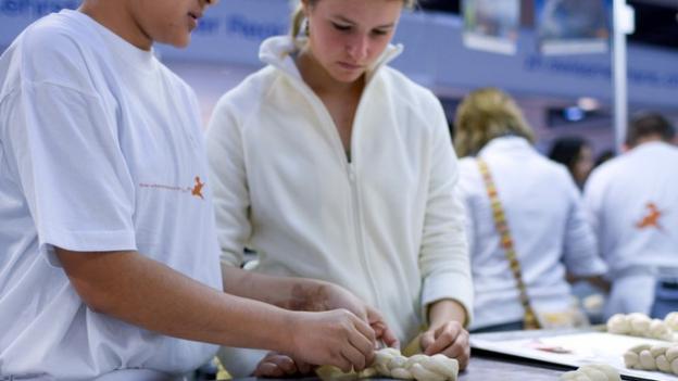 Jugendliche an einer Berufsmesse beim Zopf backen