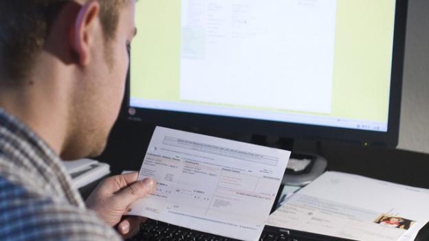 Ein Mann vor einem Computer. Er bezahlt Rechnungen.