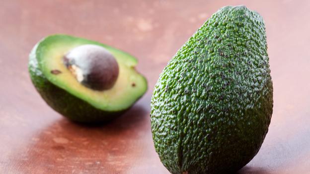 Ganze Avocado, im Hintergrund unscharf eine aufgeschnittene Frucht.